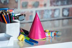 Party horn, birthday hat, pen holder and spectacle on desk Stock Photos