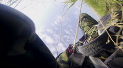 Parachutist in camouflage suit hitting hard the ground. View from the camera - stock footage