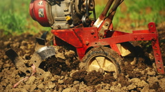 Man preparing garden soil with cultivator tiller Stock Footage
