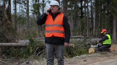 Forest Officer with smartphone and worker start fixing chainsaw Stock Footage