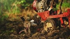 Man preparing garden soil with cultivator tiller on organic vegetable farm - stock footage