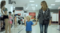 Young attractive mother with adorable child walking in mall along window display Stock Footage