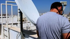 Technician  adjusting  of a satellite television plate Stock Footage