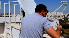 Technician  adjusting  of a satellite television of a satellite dish Stock Footage