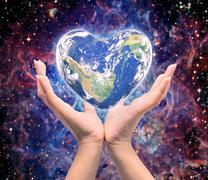 World in heart shape with over women human hands on blurred natural backgroun - stock photo