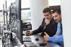 Concerned stock traders in trading office. - stock photo