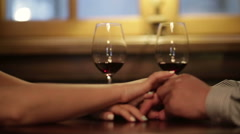 Close up of loving couple holding hands and clinking glasses of red wine during Stock Footage