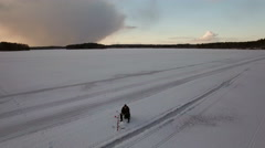 Fisherman ice fishing at a frozen lake in Finland Stock Footage