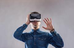 Man wearing virtual reality goggles. Studio shot, gray backgroun - stock photo