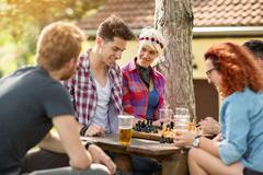 Youth at camp amused playing chess - stock photo