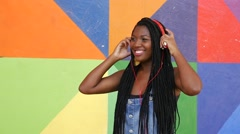Brazilian afro woman listing to music on colorful background Stock Footage