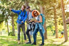 Girl with fellows look at map in forest - stock photo