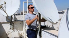 Technician adjusting a satellite television plate Stock Footage