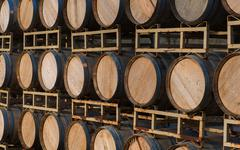 Row of wine barrels on stand - stock photo