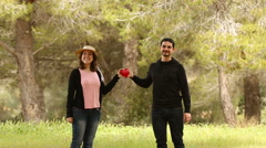 man giving a heart shape to his girlfriend in the park - stock footage