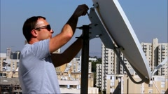 Technician  fixing of a satellite dish on the buildin roof Stock Footage