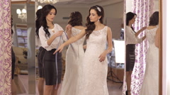 The consultant helps the girl to choose a wedding dress - stock footage