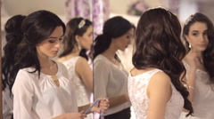 The consultant helps the girl to choose a wedding dress Stock Footage