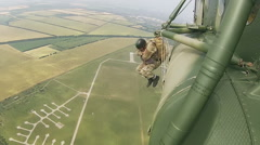 Military training of paratrooper jumping with parachutes out of helicopter Stock Footage