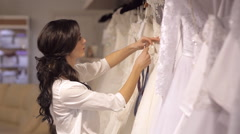 Wedding Salon consultant helps the girl to choose the dress - stock footage
