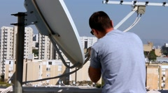 Technician setting up satellite television dish Stock Footage