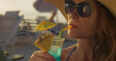 Woman in Hat and Sunglasses Drinking Cocktail Stock Footage