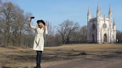 Girl doing selfie in the park against the backdrop of a beautiful building Stock Footage