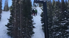 Two people on a chairlift with trees on a sunny day Utah Park City USA Stock Footage