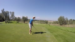 Man playing gold teeing off with driver on mountain course Tuscany Italy Stock Footage