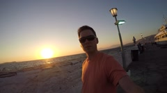 Man taking selfie in Mykonos Greece downtown beach port sunset selfie stick ugc Stock Footage