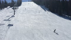 Skiers going down a slope on a sunny day shot from chairlift in Park City Utah Stock Footage