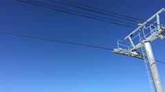 Orange bubble chairlift as it passes over a column on sunny day Park City Utah Stock Footage