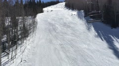 Skiers going down a slope on a sunny day shot from chairlift Park City Utah USA Stock Footage