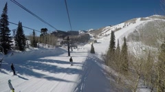 GoPro Skiers going down a slope on a sunny day shot from chairlift Park City Stock Footage