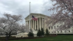 United States Supreme court front sitde with US flag at half mast and cherry Stock Footage