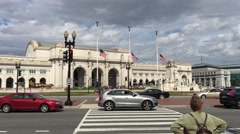 Union Station Washington D.C. flags flow at half mast with traffic train station Stock Footage