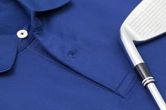 Blue polo shirt and golf equipments - stock photo