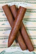 US dollar banknotes and Cuban cigars - stock photo