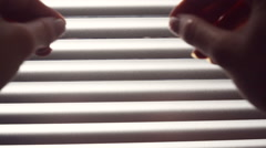 Female hand separating slats of venetian blinds with a finger to see through Stock Footage