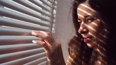 Woman hand pushing the blinds and looking out window Stock Footage