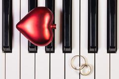 Piano keyboard,red heart and wedding rings Stock Photos