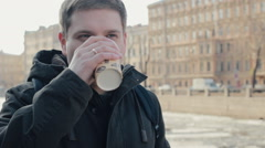 Pensive young man enjoying the coffee on the street near the river Stock Footage