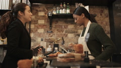 4K Cheerful worker serving young professional who uses smartphone to pay in cafe - stock footage