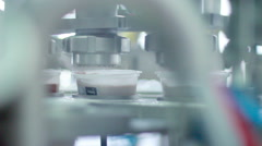 Yogurt is poured into the package. Food packaging line at dairy factory Stock Footage