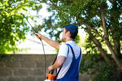 Rear view of pest control worker - stock photo