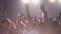 People raise hands on rock concert in nightclub. Band performing on stage Stock Footage