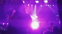 Back side of dancing girl in crowded nightclub. Clapping. Pink bright spotlight Stock Footage