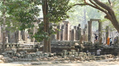 Monk and other tourists around the Bayon Khmer temple Stock Footage