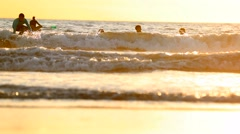 Surfer riding wave during sunset time. Surfers at the beach during golden hour Stock Footage