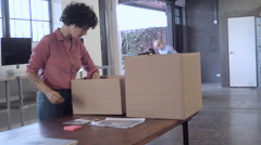 Business people packing boxes in office Stock Footage